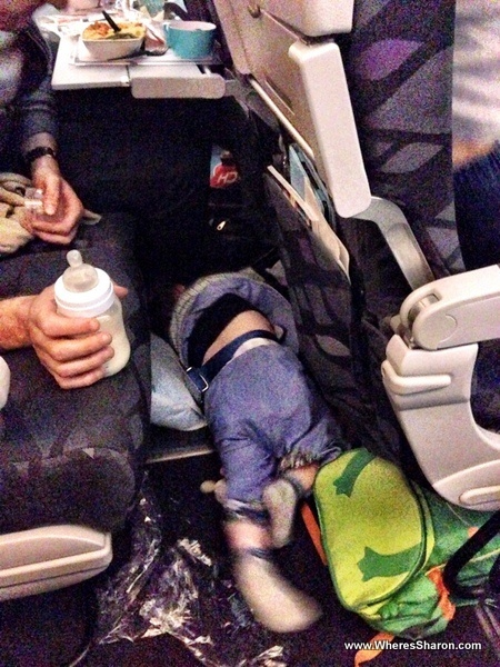 infant having a tantrum on the plane on the floor in front of the seats
