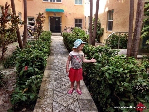 toddler standing playing with planets in south beach apartment complex