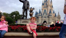 toddler posing in front of cinderellas castle and mickey mouse statue at magic kingdom disneyworld