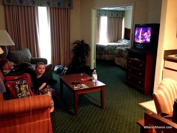 Lounge room and couch with bedroom in background at palms hotel and villas kissimmee