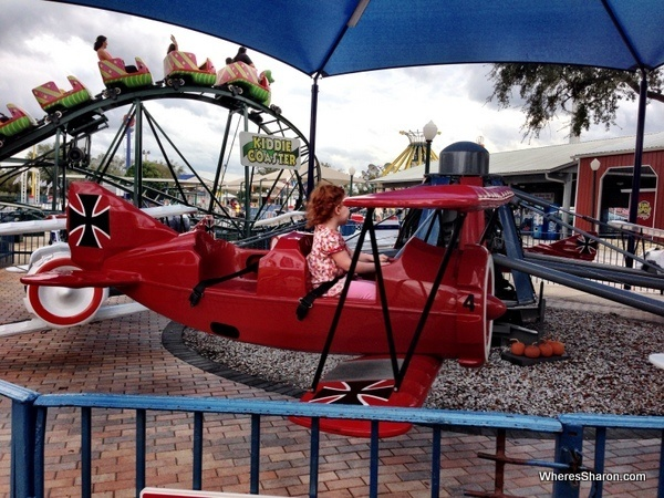 S flying in plane with a roller coaster in the background at fun spot usa