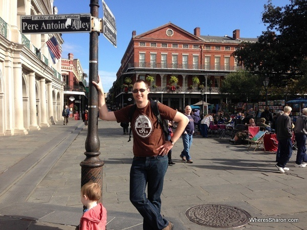 Man leaning on street post with square and lovely buildings behind him in French Quarter
