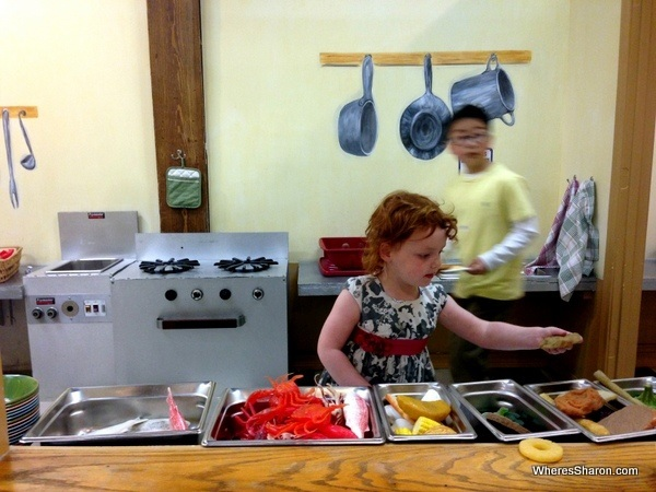 Kid using plastic food to make food with toy oven in louisiana's children museum