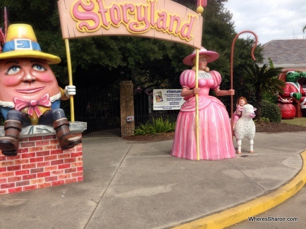 S sitting on lamb with big sign saying story land