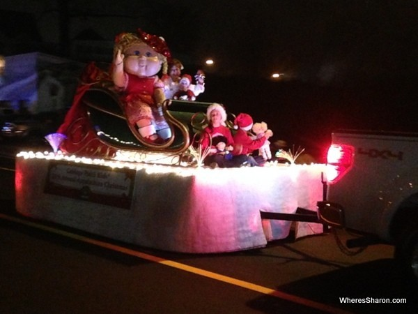 Big cabbage patch kid on a float in christmas parade at night