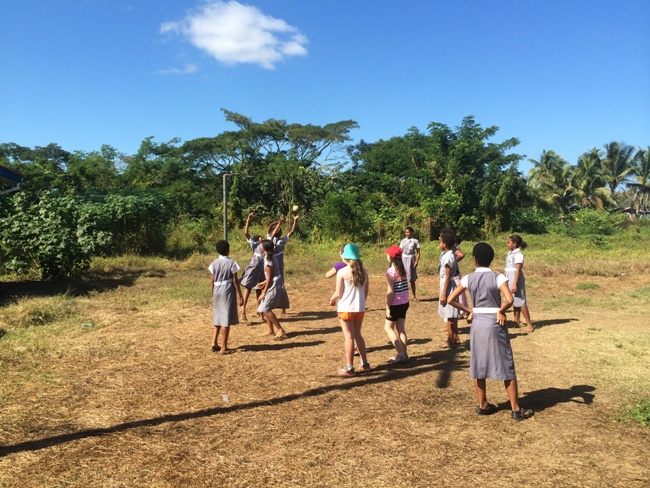 Visitors joining students in a netball game at a Fijian school